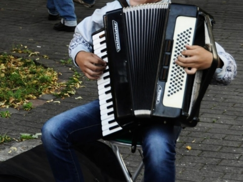 Young street basker playing the accordion in Vilnius, Lithuania